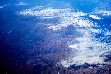 Beautiful aerial view of the land, fields, and clouds from above