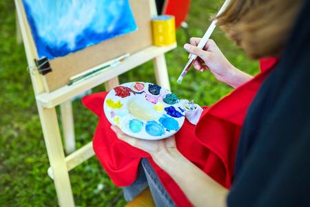Multicolored gouache paints, brush, palette, female hand of the artist.