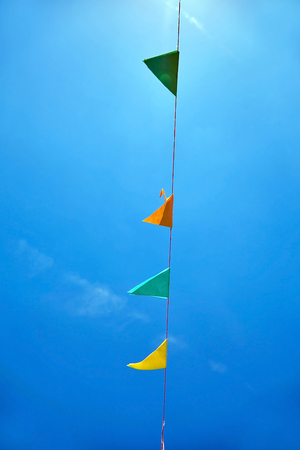 Multicolored triangular paper festival flags on blue sky background. 版權商用圖片