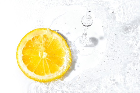 Bright yellow fresh lemon slice and water splash. Tasty and healthy food Stok Fotoğraf