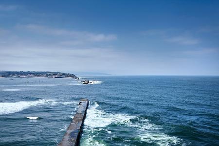 Saint Jean de Luz, France. Basque country. City views Ciboure and Castle and port of Socoa. Ocean waves breaking about the dam (Digue de Sainte-Barbe)