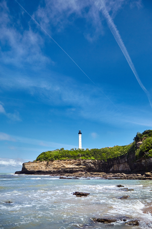 Biarritz, France. Sand beach Miramar Plage overlooking the white lighthouse - Phare de Biarritz on the Pointe Saint-Martin. Bay of Biscay, Atlantic coast, Basque country. Sunny summer day Stock Photo