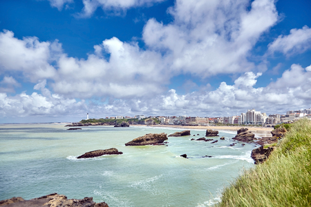 Biarritz city and ocean waves. Bay of Biscay, Atlantic coast, Basque country, France. Summer sunny day and blue sky with white clouds
