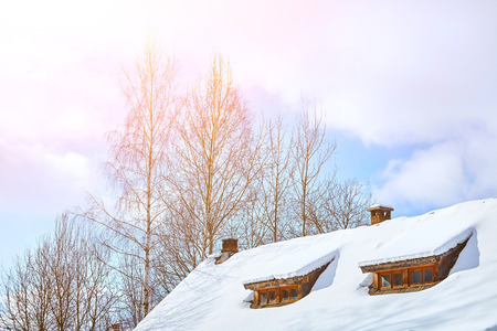 Roof of a low-rise wooden village house with windows under the snow. Winter. Trees and blue sky with clouds in the background