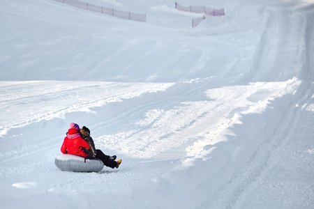 Mother and son sliding on snow tubing down the hill. Woman and boy having fun sledding on a tube at winter day