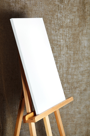 pure white synthetic canvas stretched on a wooden stretcher standing on a wooden easel for artists. On sackcloth fabric texture background. Art, creativity, hobby, job and creative occupation concept Stock Photo