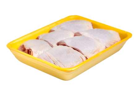Raw and uncooked chicken thighs in a yellow plastic container. Meat of poultry in tray, isolated on white background Standard-Bild