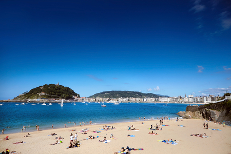 People having a rest on a sandy beach. Seaside resort. Summer sunny day. La Concha Bay in San Sebastian (Donostia), Basque country, Spain