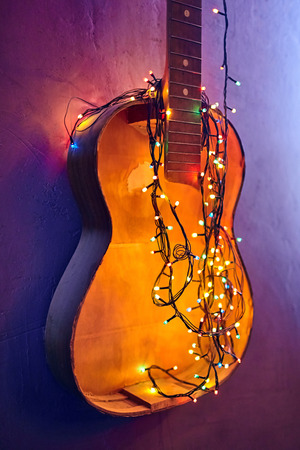 Old broken wooden guitar decorated bright glowing garland. Musical instrument hanging on the wall. Christmas interior decoration. Festive mood. Yellow New Year light bulbs