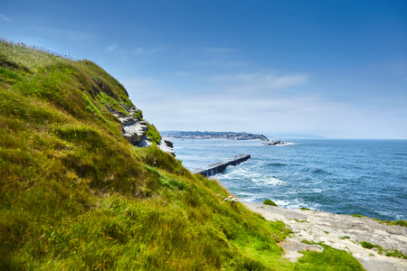Saint Jean de Luz, France. Basque country. City views Ciboure and Castle and port of Socoa. Green grass on the hill and ocean waves breaking about the dam. Seascape Stock Photo