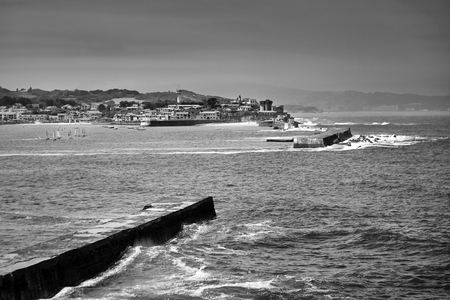 Saint Jean de Luz, France. Basque country. City views Ciboure and Castle and port of Socoa. Sailboats. Ocean waves breaking about the dam. Black and white photography