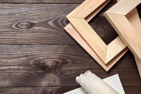 Wooden stretchers and a rolled canvas lying on a dark wooden background with copy space. Wood products: Subframes. Top view Foto de archivo
