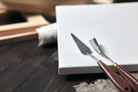 Artist tools: Palette knives lying on a white primed cotton canvas. wooden stretchers in the blurred background. Selective focus Foto de archivo