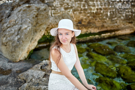 Portrait of a young  woman with long brown hair. Caucasian girl sitting on stones in a white dress and hat on head against the background of an old stone wall and sea water Imagens