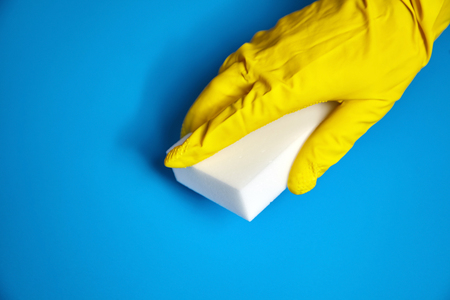 Human hand in yellow glove holds a white melamine household sponge on blue background