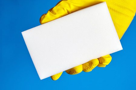 Human hand in yellow rubber glove holds a white melamine sponge on blue background