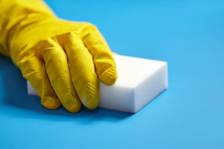 Human hand in yellow glove holds a white melamine sponge on blue background