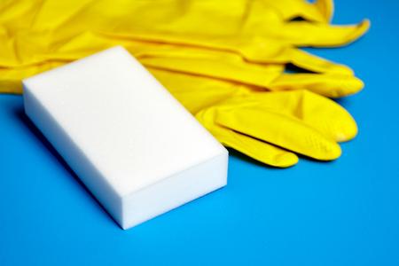 Yellow gloves and white melamine sponge on blue background
