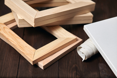 Wooden stretcher bars and a rolled canvas lying on a dark brown background, timber, subframes Stockfoto
