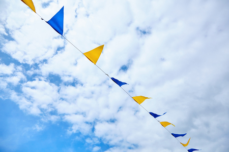Yellow and blue triangular festival flags on sky background with white clouds. Outdoor Celebration Party. Festive mood