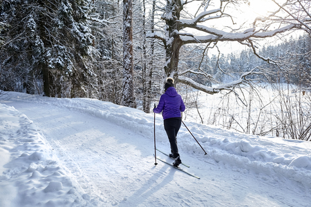 A woman cross-country skiing in the winter forest, skier among snow covered trees