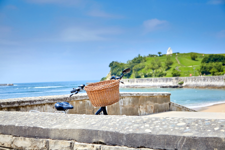 Bicycle with a basket parked on a stone embankment of Saint Jean de Luz against the background Pointe Saint Barbe (Basque Country, Atlantic coast, France)