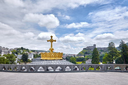 Lourdes, France: The Sanctuary of Our Lady of Lourdes is one of the largest pilgrimage centers in Europe. The Golden Crown and the Cross on the Dome of The Basilica of Our Lady of the Rosary