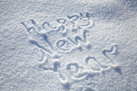 Inscription Happy New Year on snowy winter background, text on snow surface