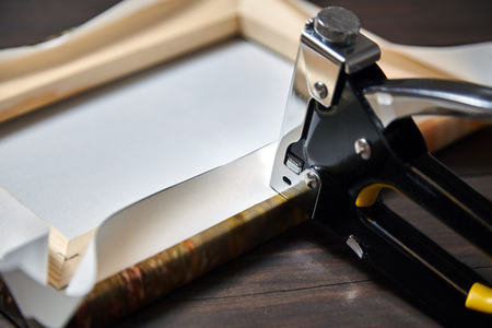 Estiramiento de lienzo sobre barra camilla de madera. Foto impresa en lienzo sintético (vista posterior) y grapadora sobre mesa de madera marrón