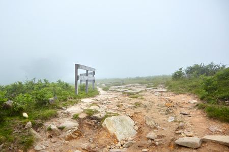 Hiking trail, wooden fence. Foggy summer day. La Rhune mountain, Basque country, France Stock Photo