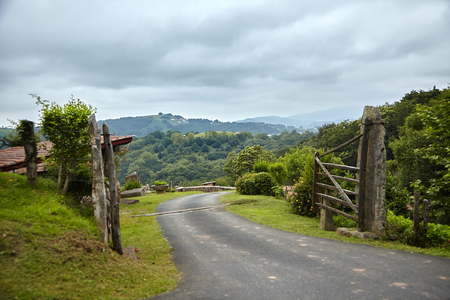 Countryside in southern France in the foothills of the Pyrenees mountains. Wooden fence with gate and rural road Stock Photo - 123903129