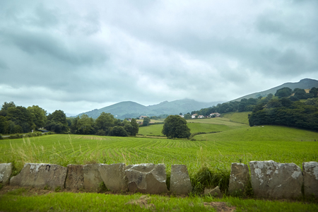 Stone fence, green fields and summer pastures. Countryside in southern France in the foothills of the Pyrenees mountains