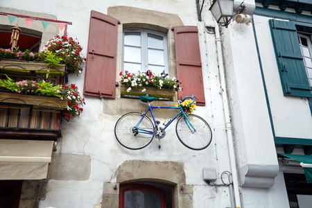 Bicycle is hanging under the window with wooden shutters on the wall of the facade of the building. Traditional red and white basque house Stock Photo - 123903132