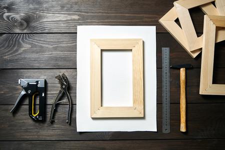Estirar el lienzo en la barra de camilla de madera, pistola de grapas y alicates de lona sobre una mesa marrón Foto de archivo