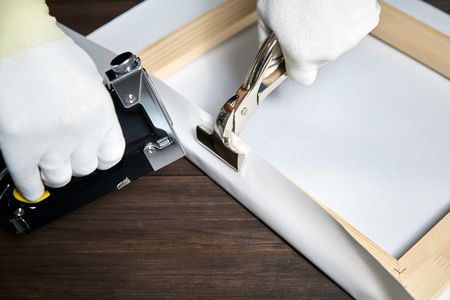 Canvas stretching. Wooden stretcher bar, staple gun, canvas pliers, male hand in white protect gloves