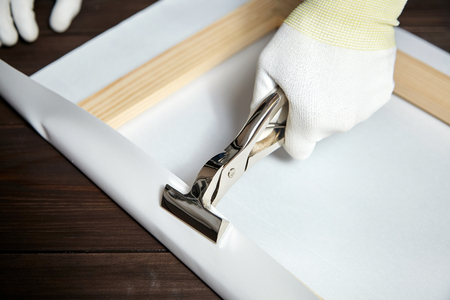 Canvas stretching process. Wooden stretcher bar, canvas pliers, male hand in white protect gloves