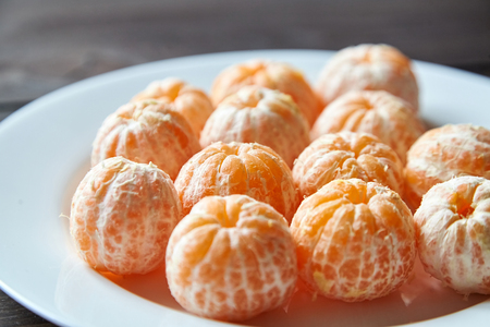Whole peeled tangerine fruits on plate