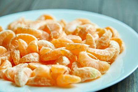 Peeled segments of tangerine on plate. Mandarin citrus fruit Фото со стока