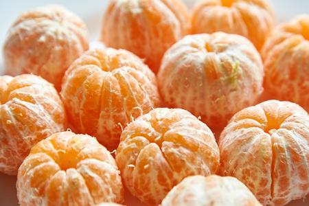 Peeled tangerine fruits. Whole mandarin citrus
