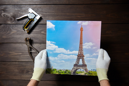 Photography printed on canvas in male hands. Image of Eiffel Tower (Paris, France)
