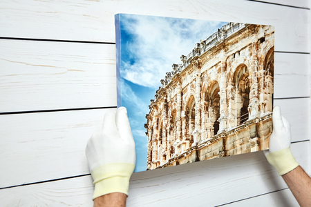 Photography printed on canvas with gallery wrap method of canvas stretching in male hands. Image of architecture of Nimes city, France