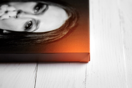 Gallery wrap, photo printed on glossy synthetic canvas and stretched on wooden stretcher bar, lateral side closeup. Selective focus