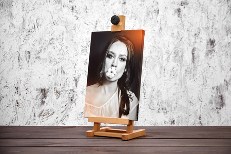 Photography printed on canvas with gallery wrap. Portrait of a beautiful young woman. Wooden easel and stretched photo canvas