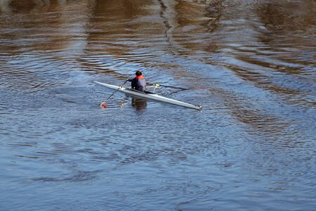 Rowing crew. Single scull rowing boat. Individual shell for one rower. Water sport