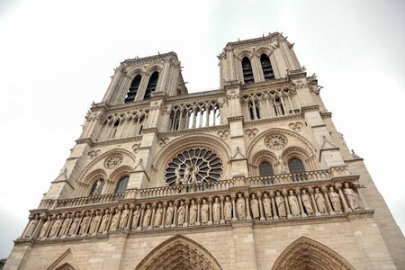Notre Dame de Paris Cathedral. Fragment of western facade with two towers and statues. Located in Paris, France