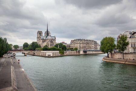 Notre Dame de Paris Cathedral (eastern facade with a spire on the roof) and river Seine in Paris (France, Europe)