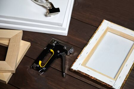 Canvas stretching on wood stretcher bar. Photo printed on canvas (back view), hammer, steel ruler and staple gun on brown wooden table Foto de archivo