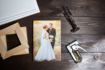 Photo of a wedding couple printed on canvas. Photography on a wooden table. Stretching canvas tools, stretcher bars