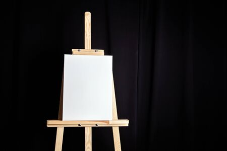 White blank cotton canvas stands on a wooden artistic easel on black curtain background. Vertical rectangular mockup canvas wrapped on stretcher bar