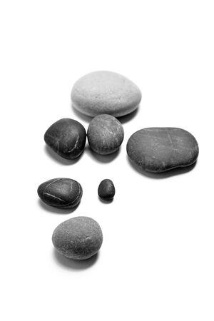 Galets de mer épars. Tas de pierres grises et noires lisses isolées sur fond blanc